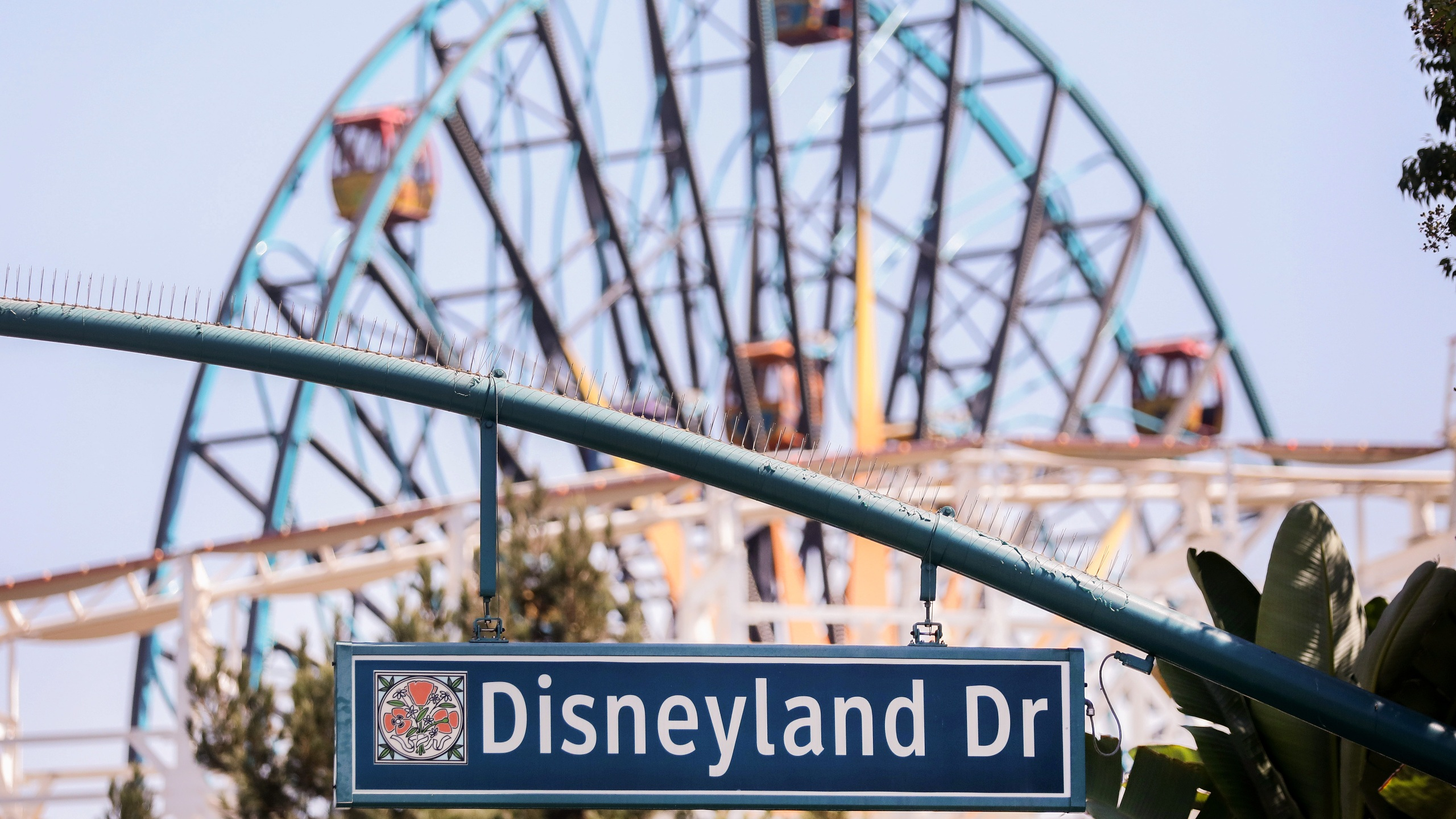 A sign for Disneyland Drive hangs near empty amusement rides on Sept. 30, 2020, in Anaheim, California.(Mario Tama/Getty Images)