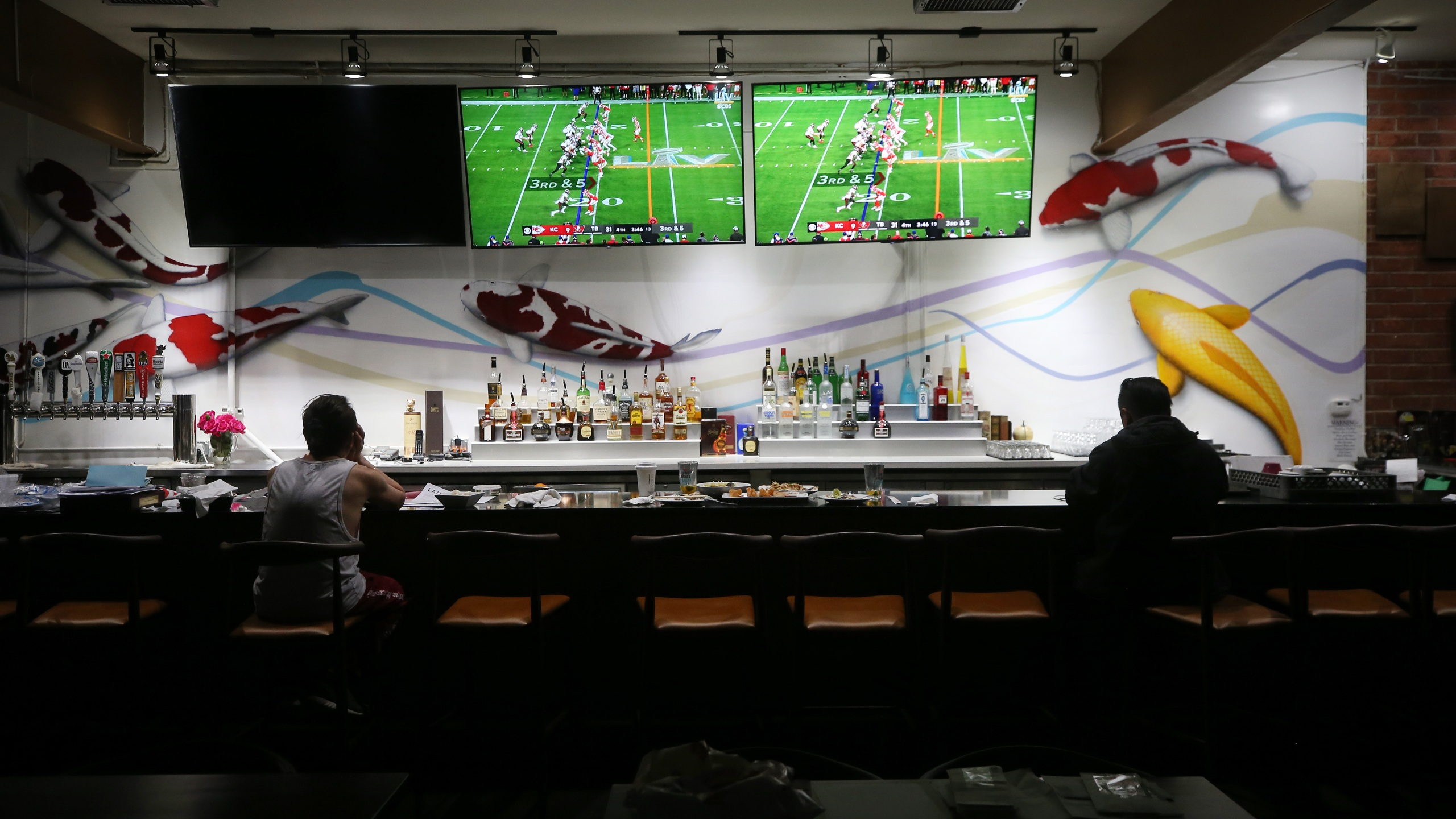 Restaurant workers sit during a break as Super Bowl LV plays on televisions in the shuttered indoor section of a restaurant on Feb. 7, 2021 in Los Angeles.(Mario Tama/Getty Images)