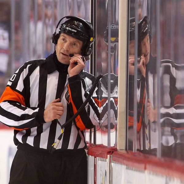 Referee Tim Peel talks with NHL officials in Toronto as they review a goal on December 17, 2011 in Glendale, Arizona. (Photo by Christian Petersen/Getty Images)