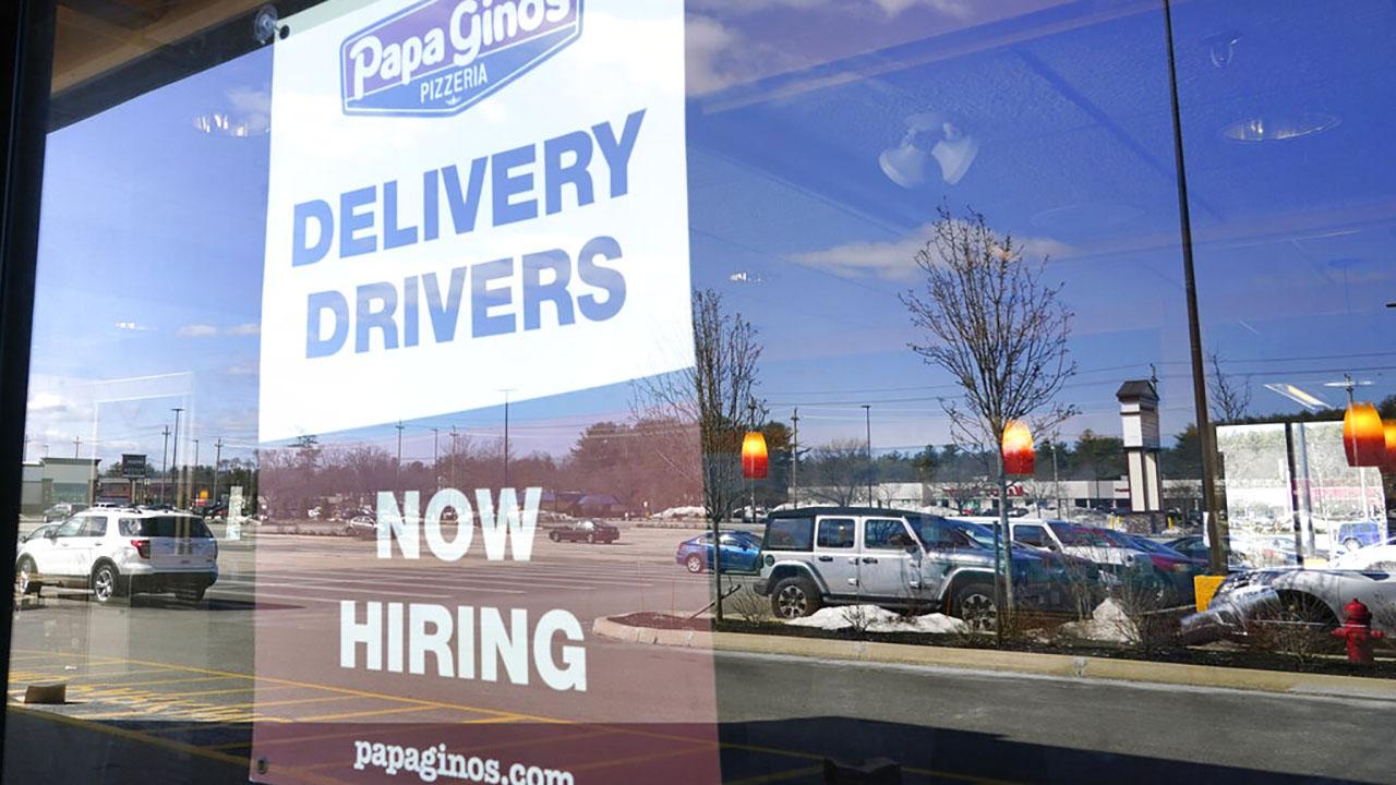 """A """"Now Hiring"""" sign is displayed, Thursday, March 4, 2021, in Salem, N.H. After a year of ghostly airports, empty sports stadiums and constant Zoom meetings, growing evidence suggests that the economy is strengthening. (AP Photo/Elise Amendola)"""