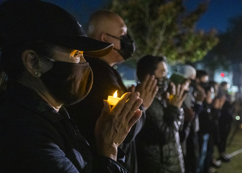 On March 23, 2021, people take part in a candlelight vigil at Community Center Park in Garden Grove, honoring the victims of the Atlanta-area spa shootings. (Allen J. Schaben / Los Angeles Times)