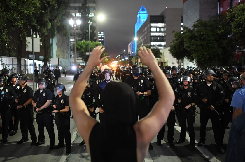 A protester faces a line of LAPD officers on Spring Street in downtown Los Angeles on May 29, 2020. (Wally Skalij / Los Angeles Times)