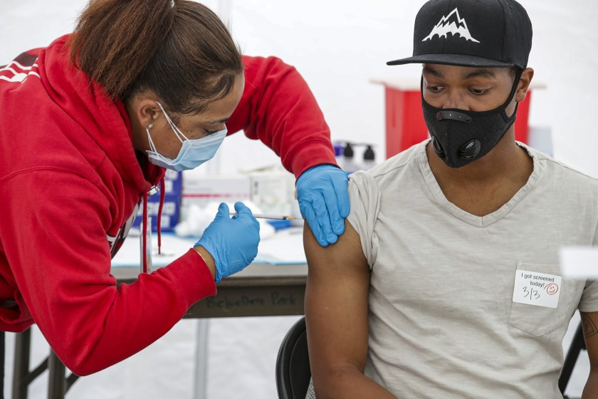 Keyaira Escoe, a medical assistant, administers COVID-19 vaccine to Xavier Scott, 26, at a site opened by St. John's Well Child and Family Center at the East Los Angeles Civic Center on March 3, 2021. (Irfan Khan / Los Angeles Times)