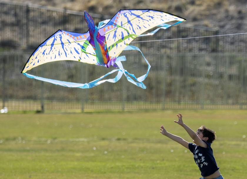 Hector Avila, 6, reaches for a kite while enjoying a windy day with his family at Anaverde Park in Palmdale.(Myung J. Chun / Los Angeles Times)