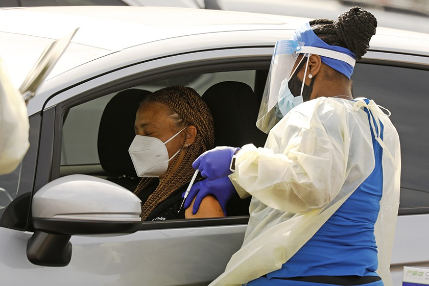 A motorist waits to be vaccinated by a health worker at the Forum, one of several mass COVID-19 vaccination sites in Los Angeles County.(Al Seib / Los Angeles Times)