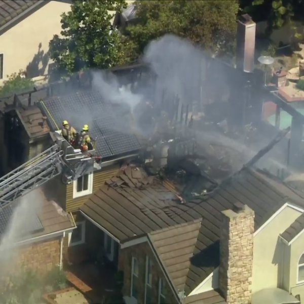 Orange County firefighters work to put out a blaze at a home in Laguna Hills on March 31, 2021. (KTLA)