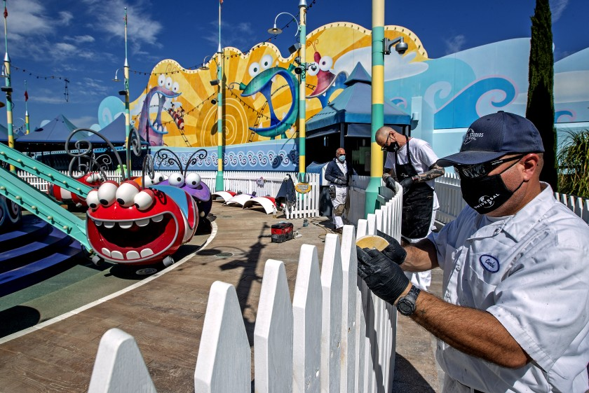 Scenic artists Billy Teichert, Jason Young and Carlos Rivas prepare to paint a fence next to a ride at Universal Studios Hollywood in this undated photo. The park, closed for more than a year, plans to open in late April. (Mel Melcon / Los Angeles Times)