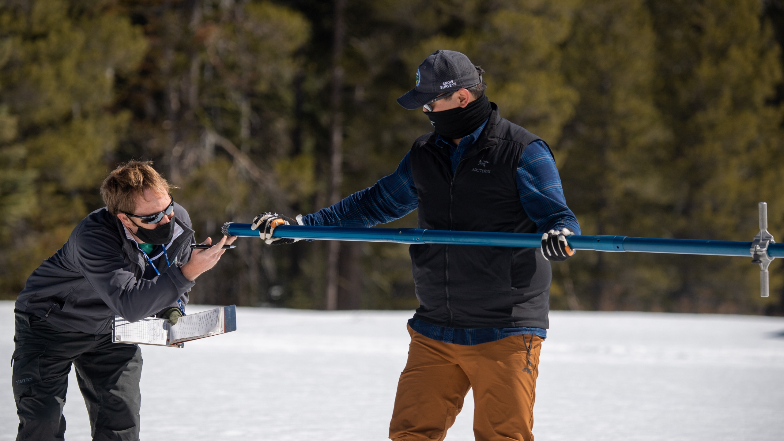 Anthony Burdock (left), Water Resources Engineer, Snow Surveys and Water Supply Forecasting Section, California Department of Water Resources, and Sean de Guzman, DWR Chief of the Snow Survey and Water Supply Forecast Section, conduct a 2021 snow survey season event at Phillips Station in the Sierra Nevada Mountains on April 1, 2021. The survey is held approximately 90 miles east of Sacramento off Highway 50 in El Dorado County. (Florence Low / California Department of Water Resources)