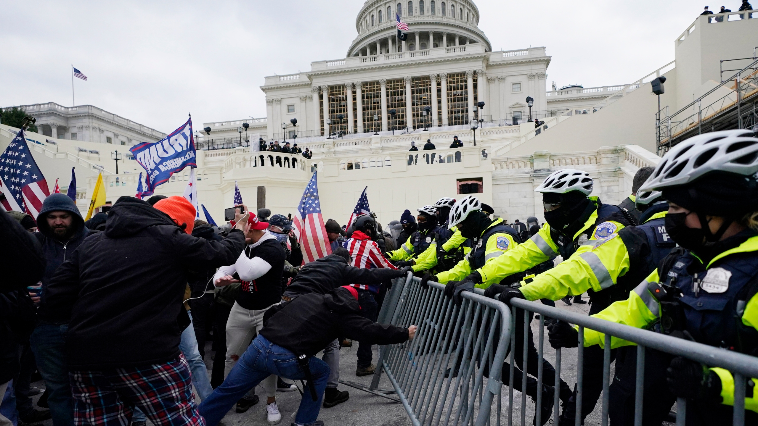In this Jan. 6, 2021 file photo, rioters try to break through a police barrier at the Capitol in Washington. (Julio Cortez/Associated Press)