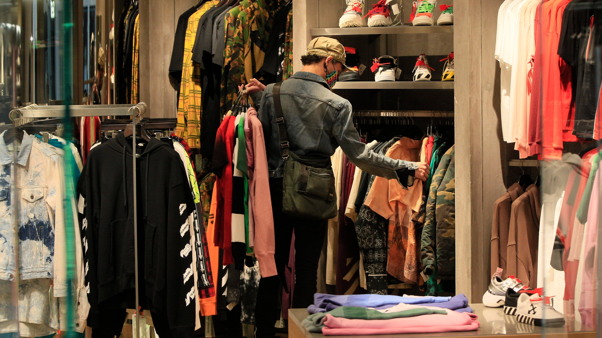 A manager at a boutique sets up new clothes for the store opening of Beverly Center shopping mall in Los Angeles on May 29, 2020. (AP Photo/Damian Dovarganes)