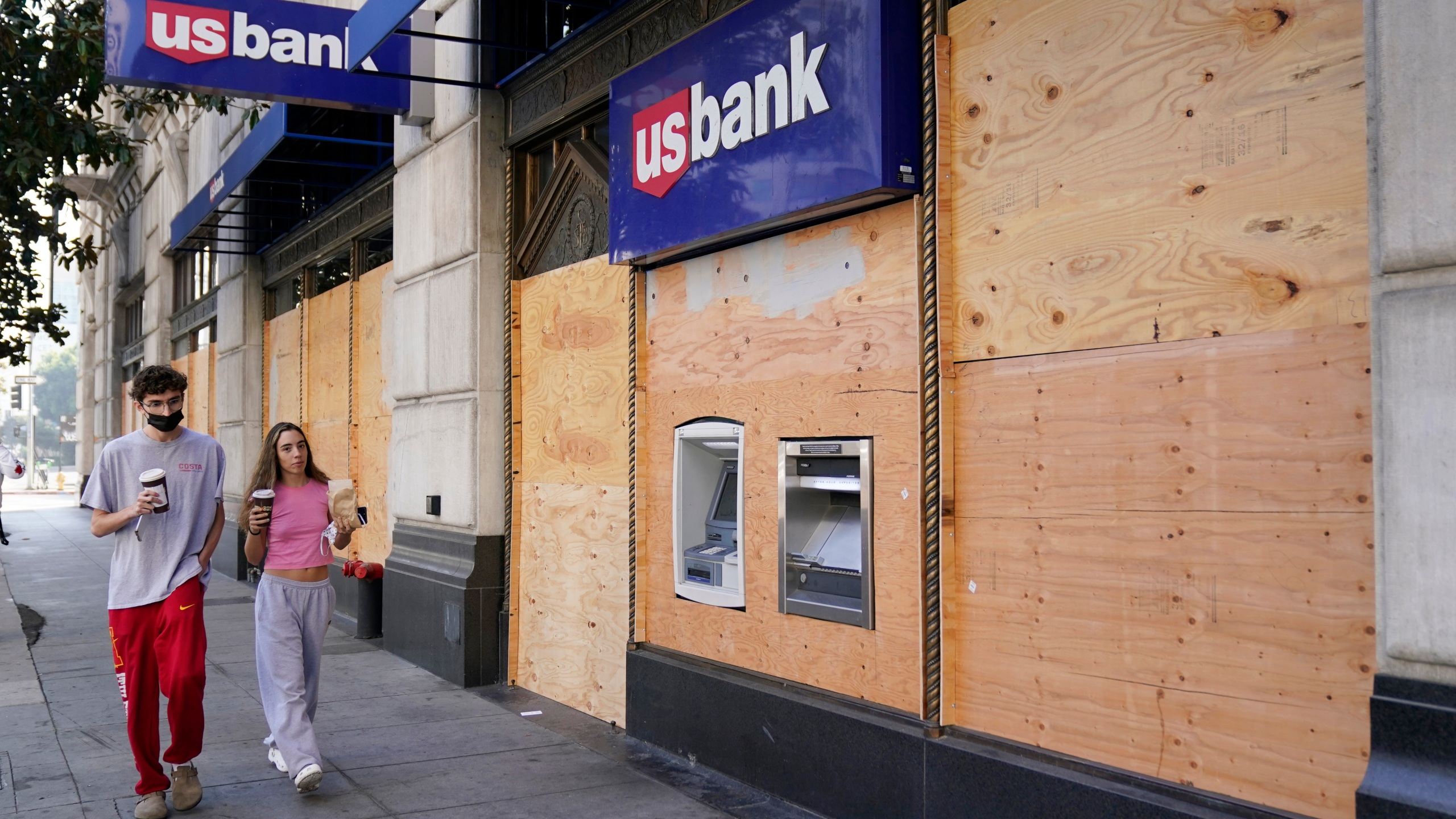 Pedestrians walk past an ATM at a boarded up US Bank branch, Monday, Nov. 2, 2020, in downtown Los Angeles. (AP Photo/Chris Pizzello)