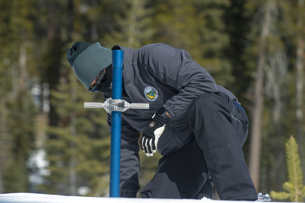 Sean de Guzman, chief of snow surveys for the California Department of Water Resources, checks the depth of the snowpack during the second snow survey of the season at Phillips Station near Echo Summit, Calif., Tuesday, March 2, 2021. (AP Photo/Randall Benton)