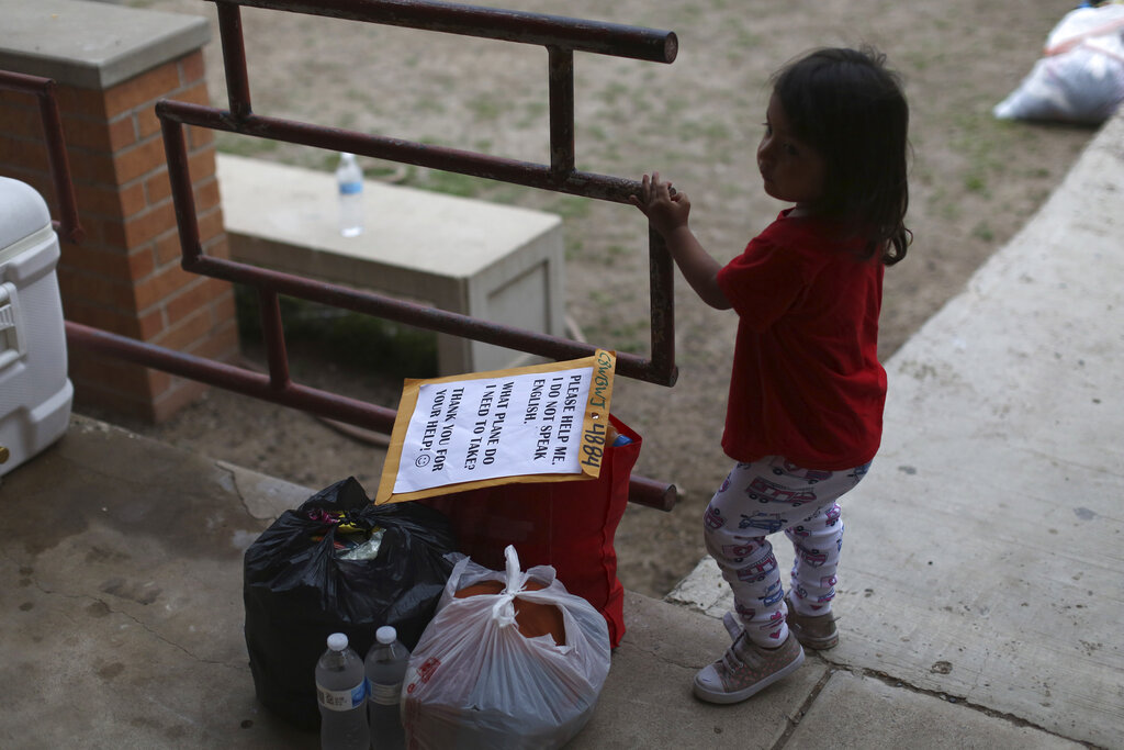 A chid stands next to her family's belongings as they wait for transportation at Our Lady of Guadalupe Catholic Church in McAllen, Texas, on Palm Sunday, March 28, 2021. (AP Photo/Dario Lopez-Mills)