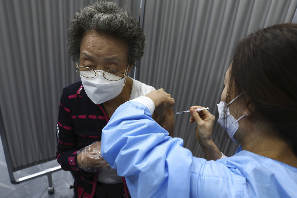 A woman receives the first dose of the Pfizer-BioNTech COVID-19 vaccine at a vaccination center in Seoul, South Korea, Thursday, April 1, 2021. (Chung Sung-Jun/Pool Photo via AP)