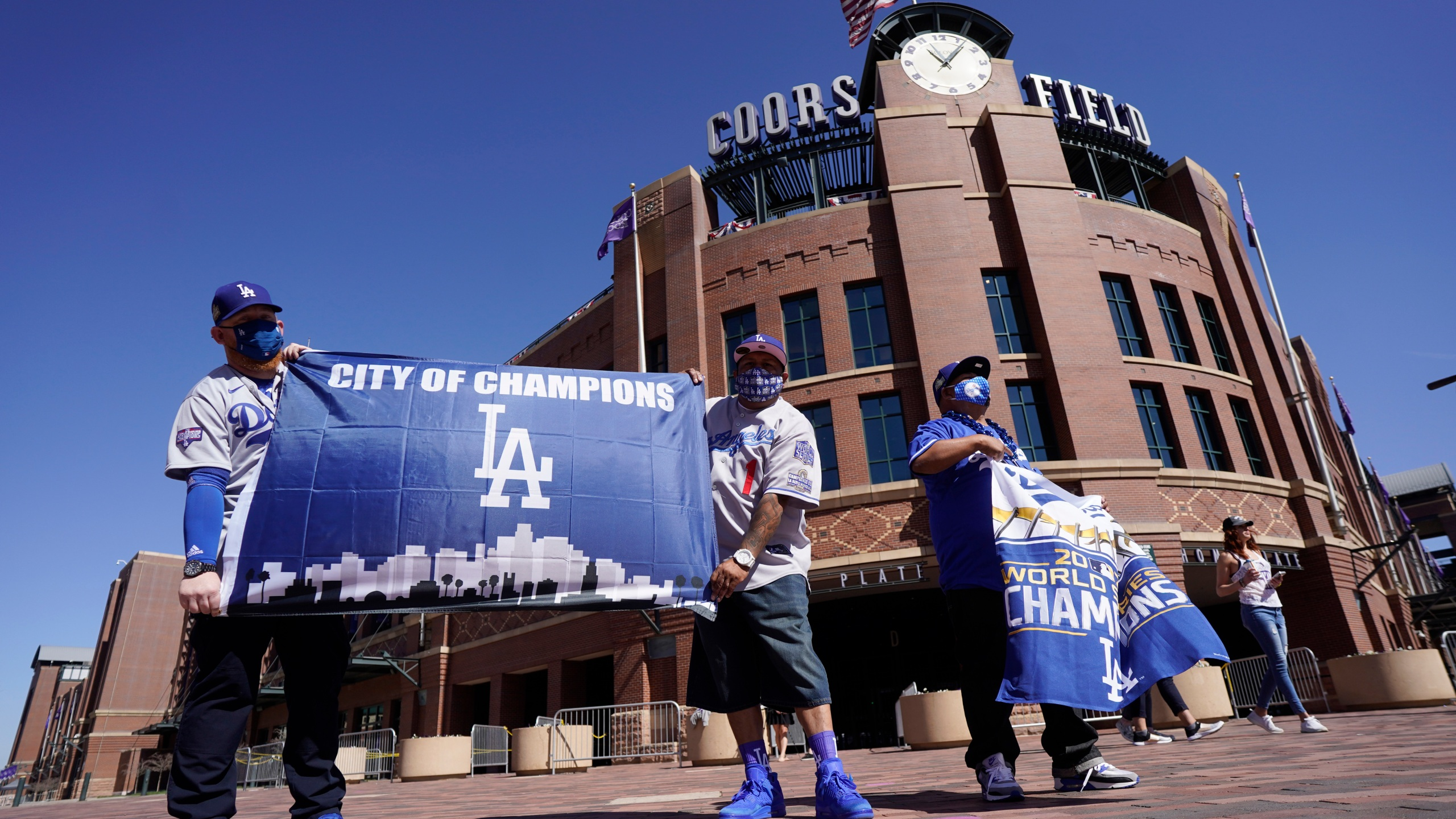 Los Angeles Dodgers fans Oliver Olson, left, of San Diego, Juan Campo and Rudy Soto, both of Los Angeles, hold up flags outside the main entrance to Coors Field in Denver as fans return for the first inning of a baseball game between the Dodgers and Colorado Rockies on April 1, 2021. (David Zalubowski / Associated Press)