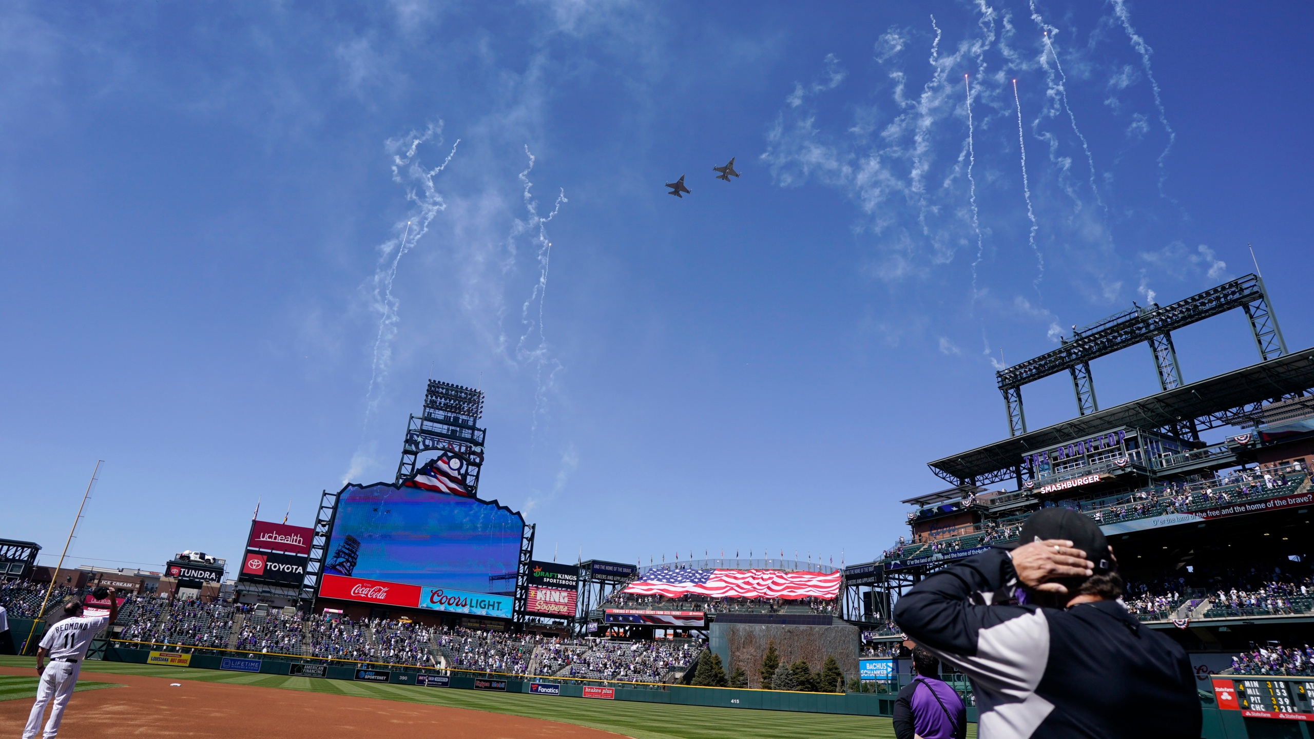 Two F-16 jets from Buckley Air Force Base in Aurora, Colo., fly over Coors Field before a baseball game between the Los Angeles Dodgers and the Colorado Rockies on opening day, Thursday, April 1, 2021, in Denver. (AP Photo/David Zalubowski)