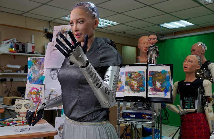 Sophia uses a brush to paint at Hanson Robotics studio in Hong Kong on March 29, 2021. (AP Photo/Vincent Yu)