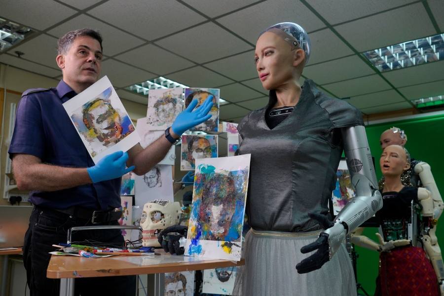 David Hanson, left, creator of Sophia, shows a work of Sophia at his studio in Hong Kong on March 29, 2021. (AP Photo/Vincent Yu)