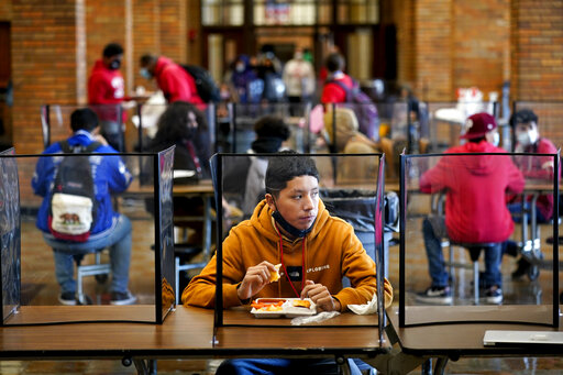 In this March 31, 2021, file photo, freshman Hugo Bautista eats lunch separated from classmates by plastic dividers at Wyandotte County High School in Kansas City, Kan., on the first day of in-person learning. With a massive infusion of federal aid coming their way, schools across the U.S. are weighing how to use the windfall to ease the harm of the pandemic — and to tackle problems that existed long before the coronavirus. (AP Photo/Charlie Riedel, File)