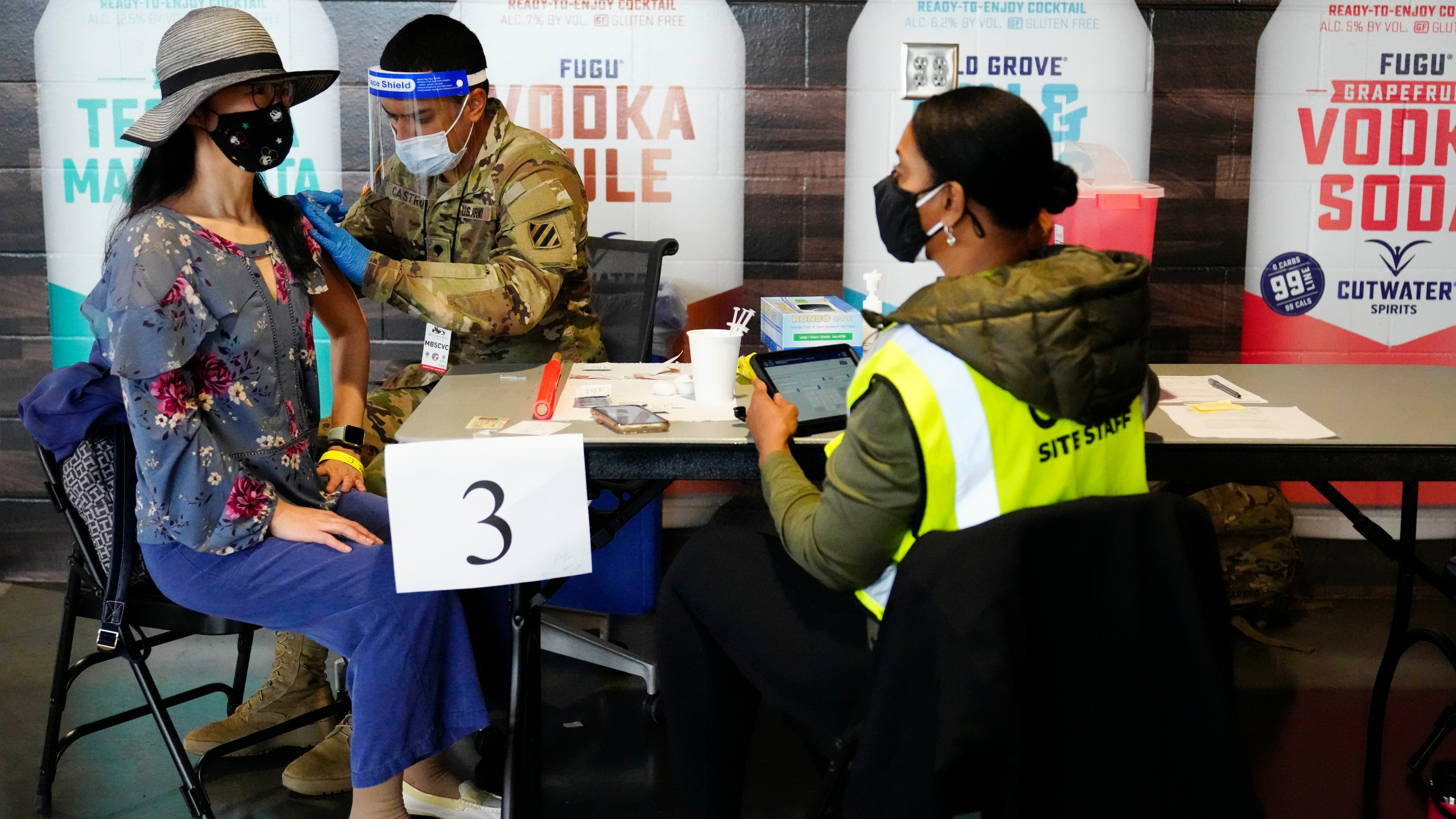In this March 25, 2021, file photo, Jing Wang, left, receives a vaccine at Mercedes-Benz Stadium in Atlanta. (AP Photo/Brynn Anderson, File)