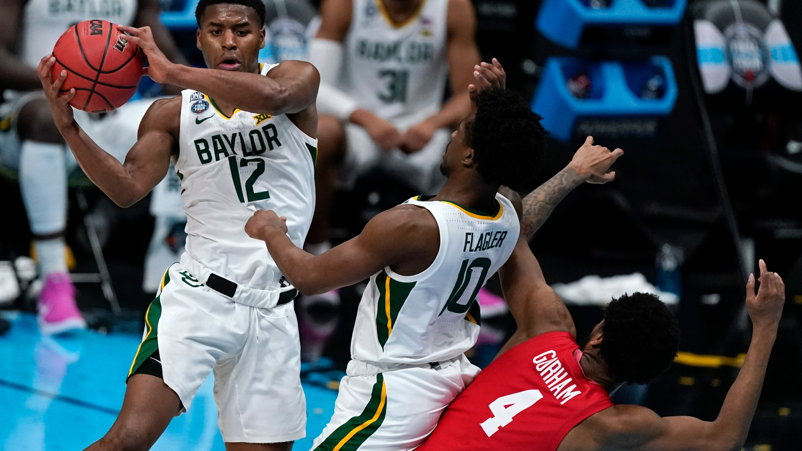 Baylor guard Jared Butler (12) passes over teammate guard Adam Flagler (10) and Houston forward Justin Gorham (4) during the first half of a men's Final Four NCAA college basketball tournament semifinal game, Saturday, April 3, 2021, at Lucas Oil Stadium in Indianapolis. (AP Photo/Michael Conroy)