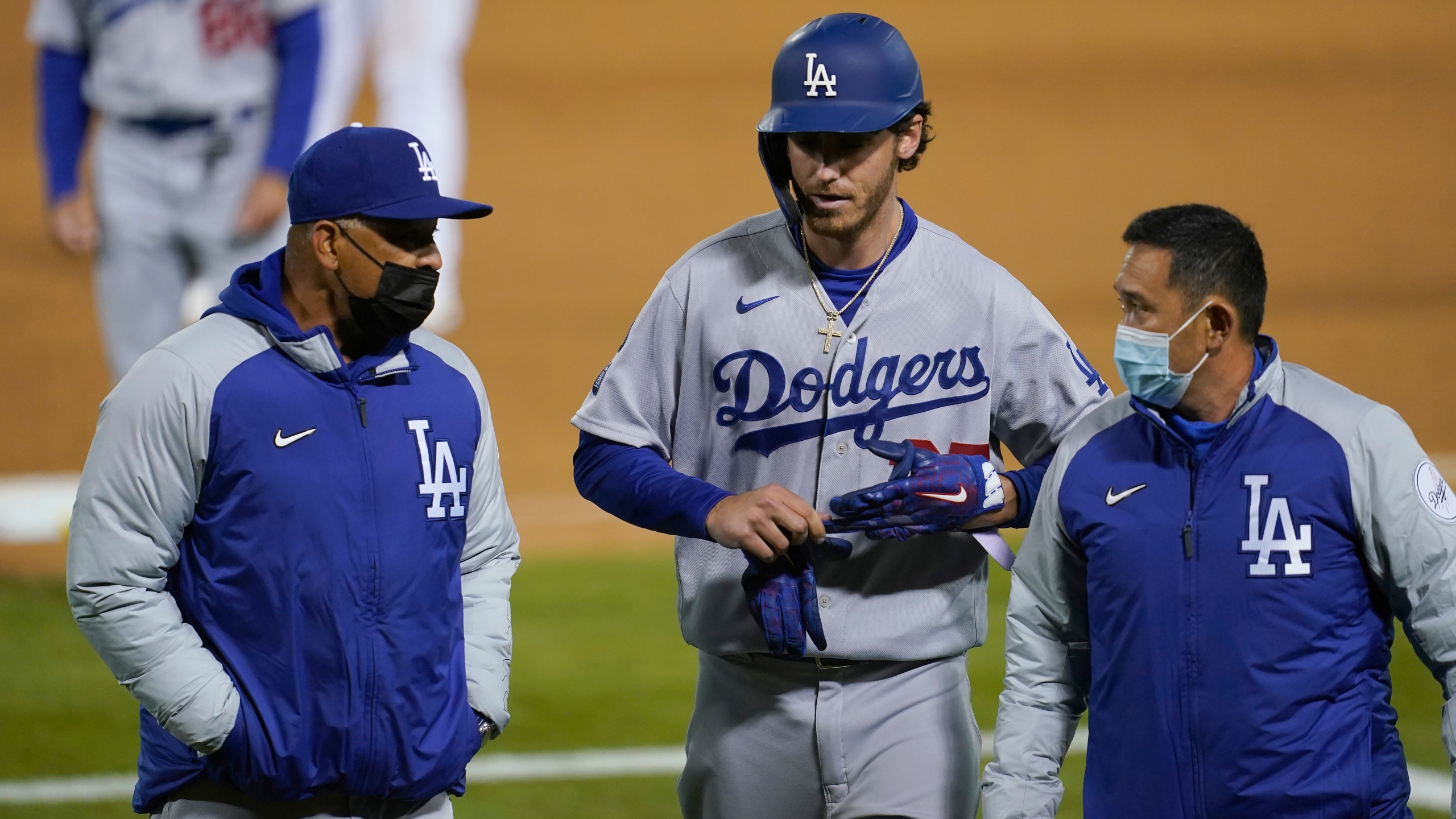 Los Angeles Dodgers' Cody Bellinger, center, walks off the field as he leaves the game with manager Dave Roberts, left, and a trainer during the ninth inning of a baseball game against the Oakland Athletics in Oakland on April 5, 2021. (Jeff Chiu / Associated Press)