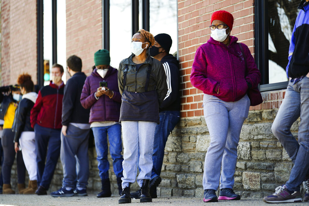 In this March 29, 2021, file photo, people wearing face masks as a precaution against the coronavirus wait in line to receive COVID-19 vaccines at a site in Philadelphia. AP Photo/Matt Rourke, File)