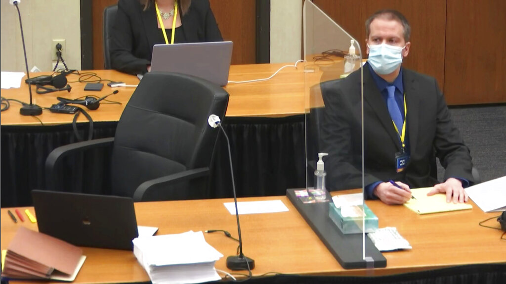 In this image taken from video, former Minneapolis police Officer Derek Chauvin watches as defense attorney Eric Nelson questions witness Los Angeles police department Sergeant Jody Stiger, Wednesday, April 7, 2021, during Chauvin's at the trial at the Hennepin County Courthouse in Minneapolis. (Court TV via AP, Pool)
