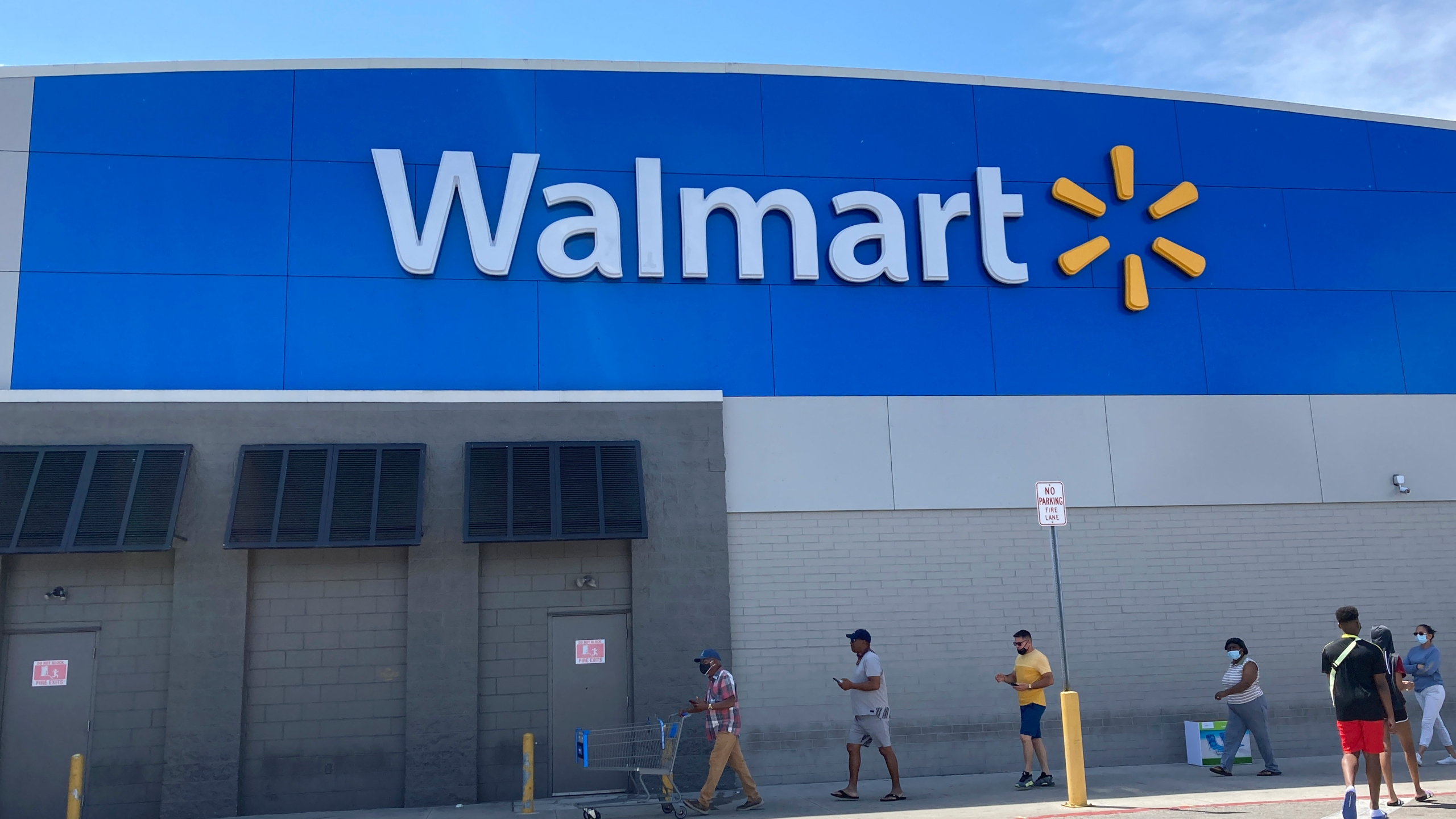 Customers wait in line outside a Walmart Supercenter store, due to COVID-19 restrictions on store capacity, Wednesday, April 7, 2021, in Miami. Walmart is moving more of its workers full time, with the goal of having two-thirds of its U.S. store hourly jobs be full-time with more consistent work schedules by early next year. With this move, announced Wednesday, April 14, the nation's largest private employer says it will have 740,000 of its 1.2 million U.S. Walmart hourly store workers be full-time by Jan. 31. (AP Photo/Wilfredo Lee)