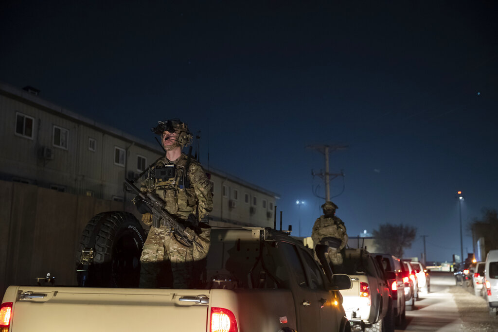 In this Nov. 28, 2019, file photo armed soldiers stand guard in the motorcade for President Donald Trump speaks during a surprise Thanksgiving Day visit to the troops at Bagram Air Field, Afghanistan. (AP Photo/Alex Brandon, File)