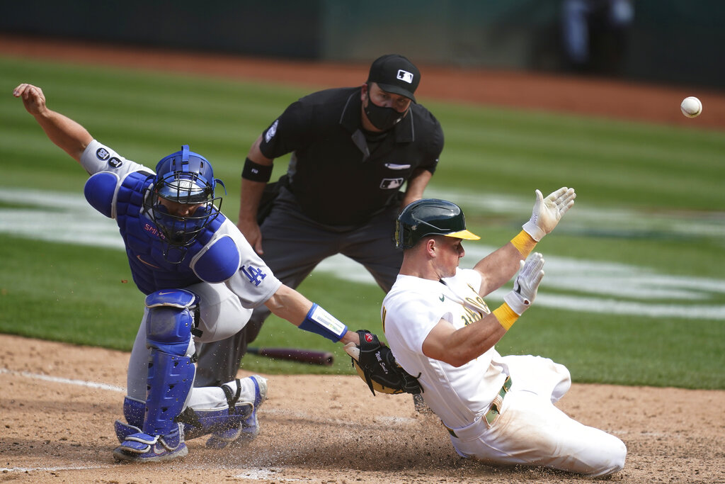 Oakland Athletics' Matt Chapman, right, slides home to score past Los Angeles Dodgers catcher Will Smith during the ninth inning of a baseball game in Oakland, Calif., Wednesday, April 7, 2021. (AP Photo/Jeff Chiu)