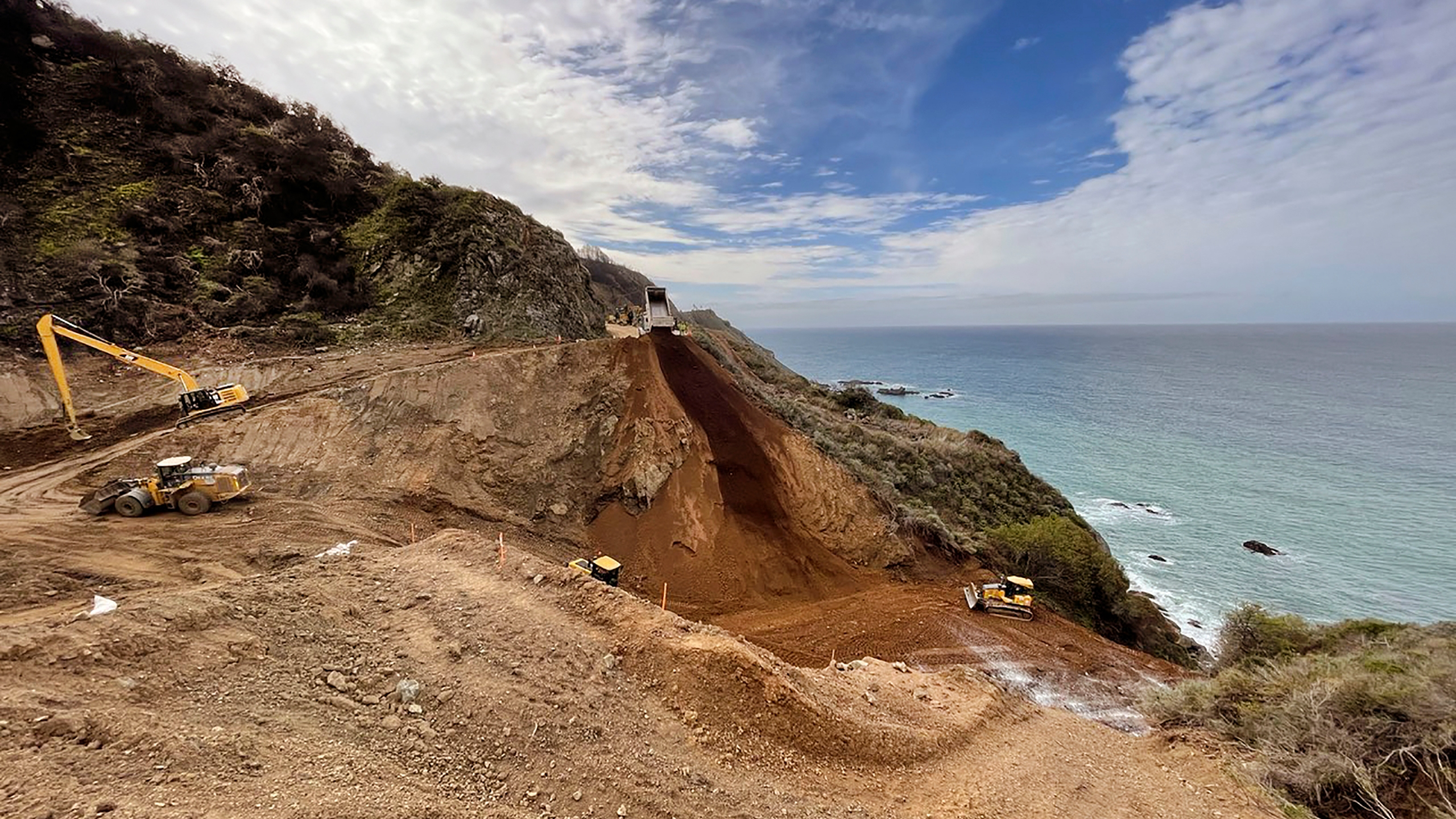 In this April 8, 2021, photo provided by the California Department of Transportation, a Caltrans construction crew repairs a section of Highway 1 along the Pacific Ocean in Big Sur, that was washed away during a winter storm on Jan. 28, 2021. The stretch of road is expected to reopen by April 30, 2021, because work to repair the huge piece of roadway that crumbled during a storm is nearly two months ahead of schedule, the California Department of Transportation announced Thursday, April 8. (Caltrans District 5 via AP)