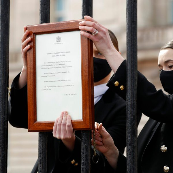 Members of staff attach an announcement, regarding the death of Britain's Prince Philip, to the fence of Buckingham Palace in London, Friday, April 9, 2021. (AP Photo/Matt Dunham)