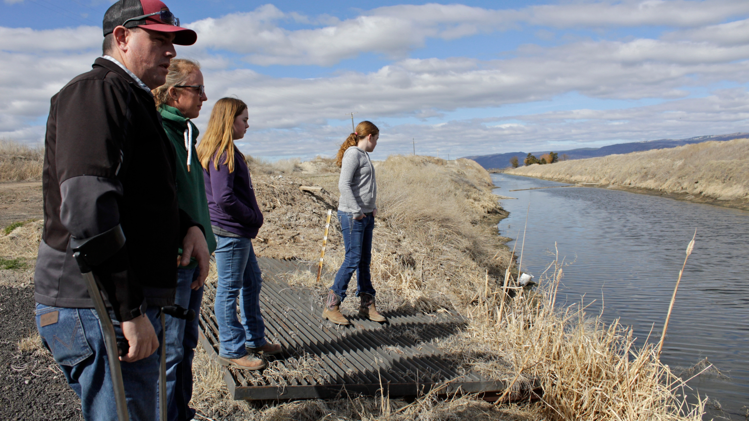 In this March 2, 2020, file photo, farmer Ben DuVal with his wife, Erika, and their daughters, Hannah, third from left, and Helena, fourth from left, stand near a canal for collecting run-off water near their property in Tulelake, Calif. (AP Photo/Gillian Flaccus, File)
