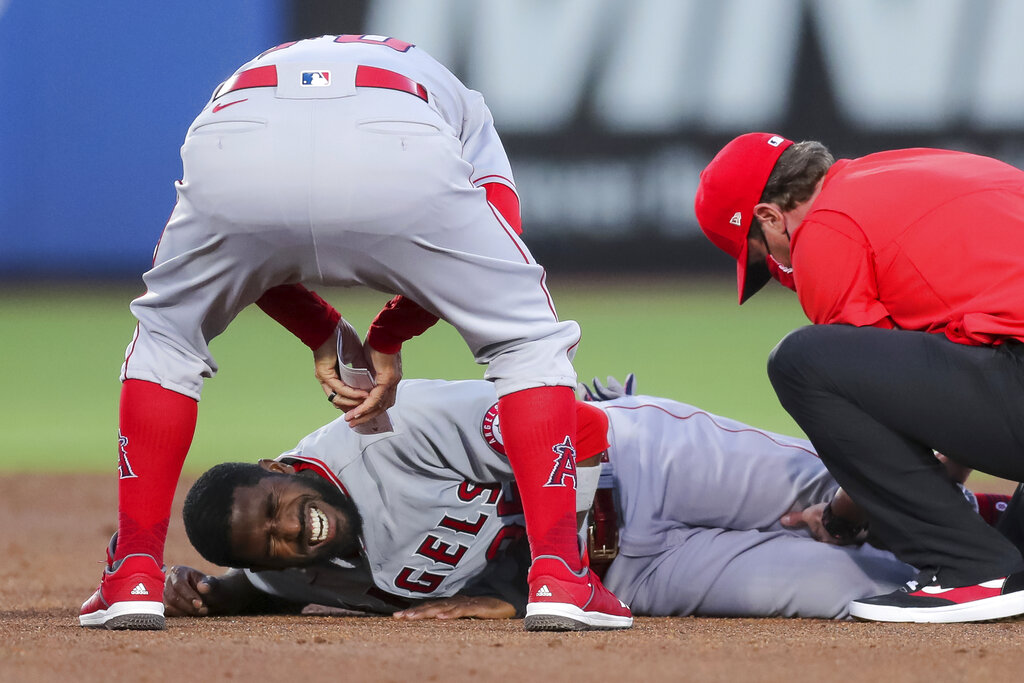 Los Angeles Angels manager Joe Maddon, top, leans over to check on Dexter Fowler who was injured during a play at second base against the Toronto Blue Jays during the second inning of a baseball game Friday, April 9, 2021, in Dunedin, Fla. (AP Photo/Mike Carlson)