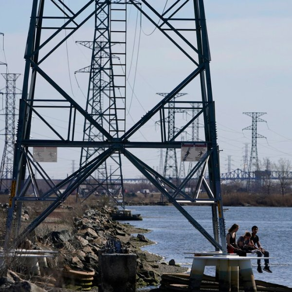 People sit at the base of a transmission tower in North Arlington, N.J., Tuesday, April 6, 2021. (AP Photo/Seth Wenig)