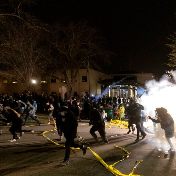 People run as police attempt to disperse the crowd at the Brooklyn Center Police Department, late Sunday, April 11, 2021, in Brooklyn Center, Minn. (Carlos Gonzalez/Star Tribune via AP)
