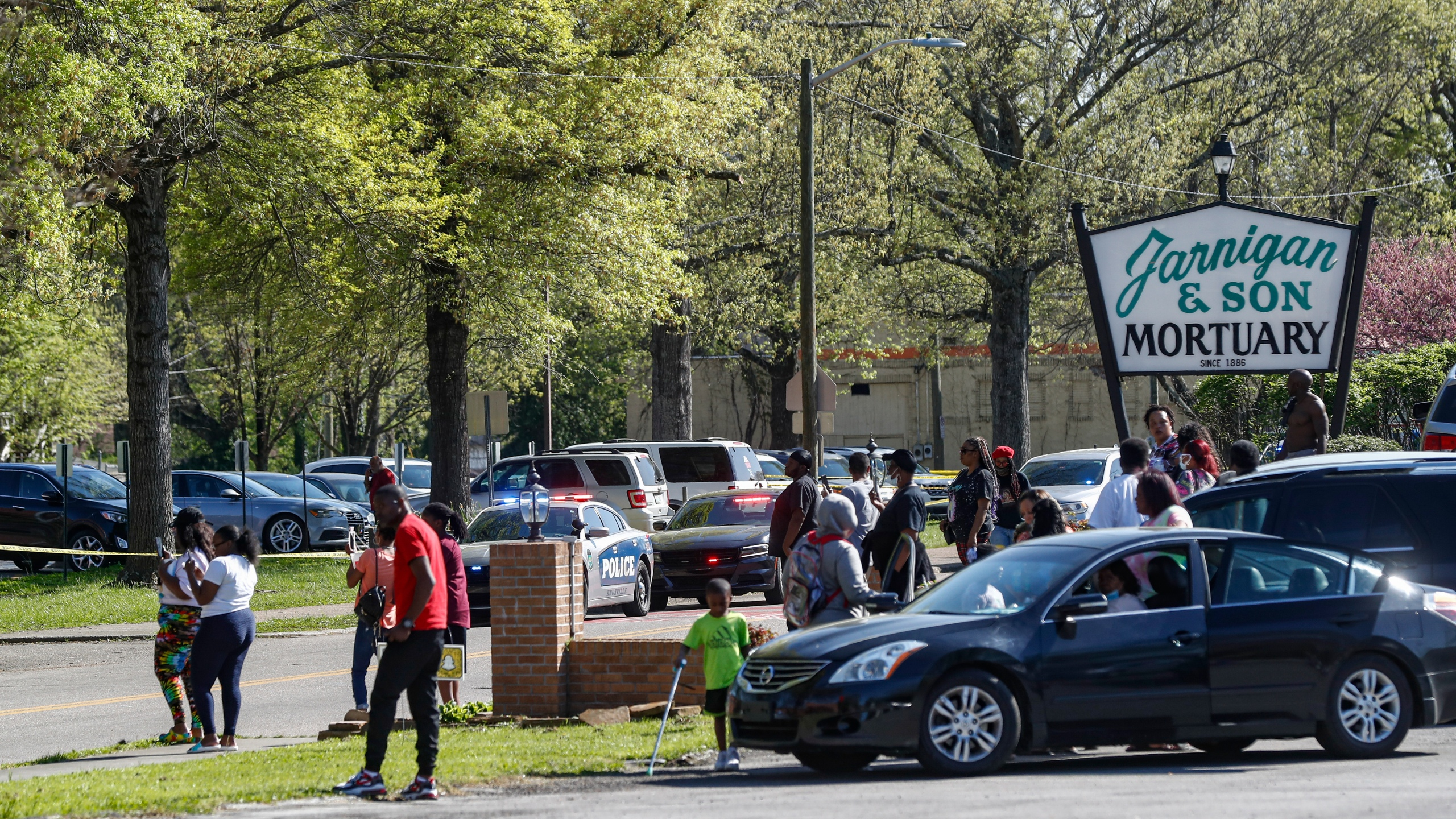People gather outside Austin-East Magnet High School in Knoxville, Tenn., following a shooting at the school Monday, April 12, 2021. (AP Photo/Wade Payne)