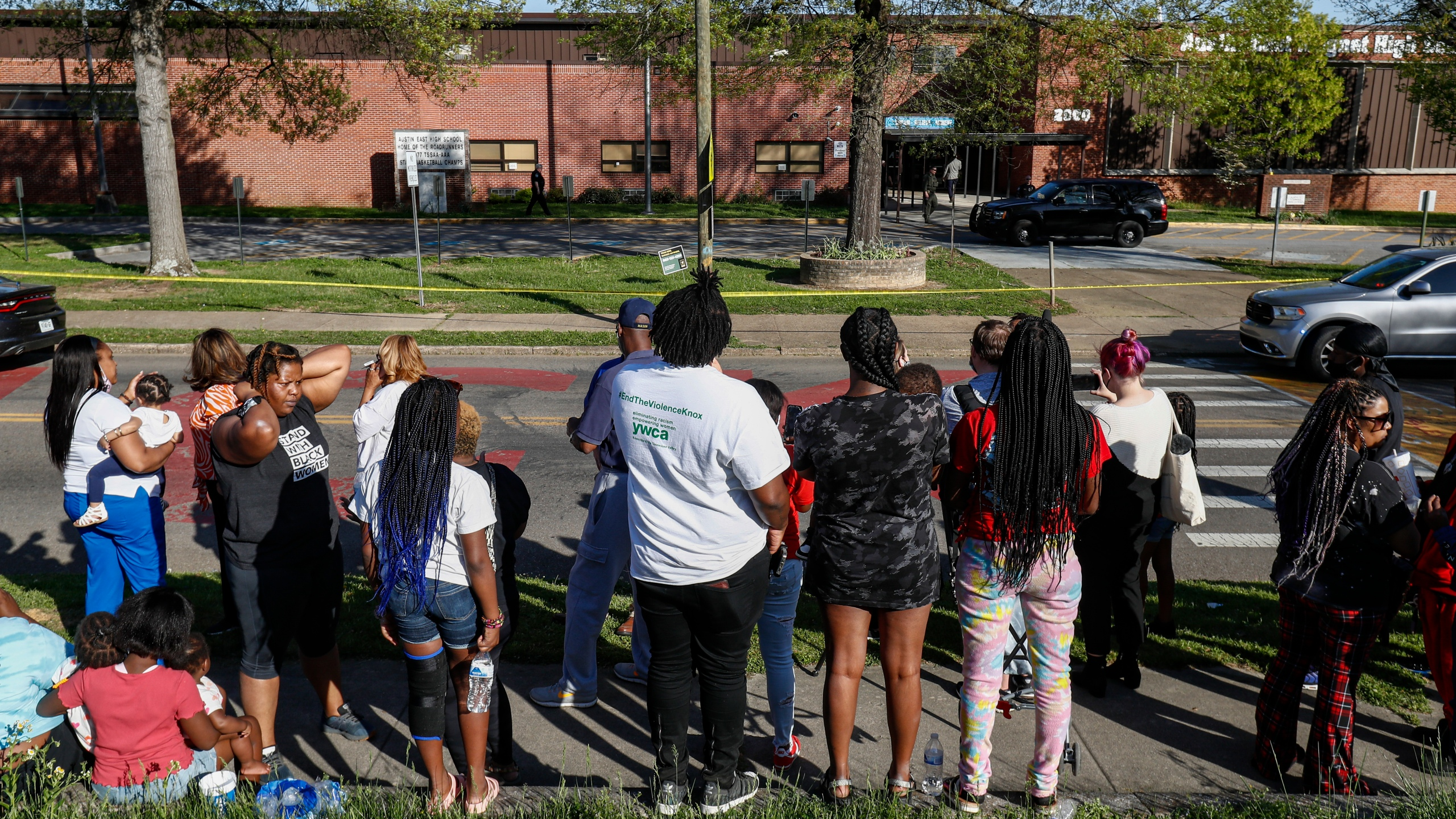 People look on as Knoxville police work the scene of a shooting at Austin-East Magnet High School in Knoxville, Tenn., on April 12, 2021. (Wade Payne / Associated Press)