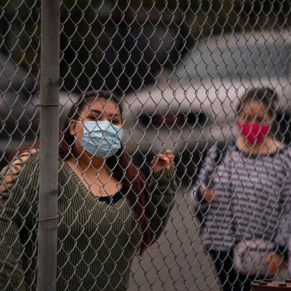 Griselda Saelak looks through a fence after dropping off her daughter on the first day of in-person learning at Heliotrope Avenue Elementary School in Maywood. (AP Photo/Jae C. Hong)