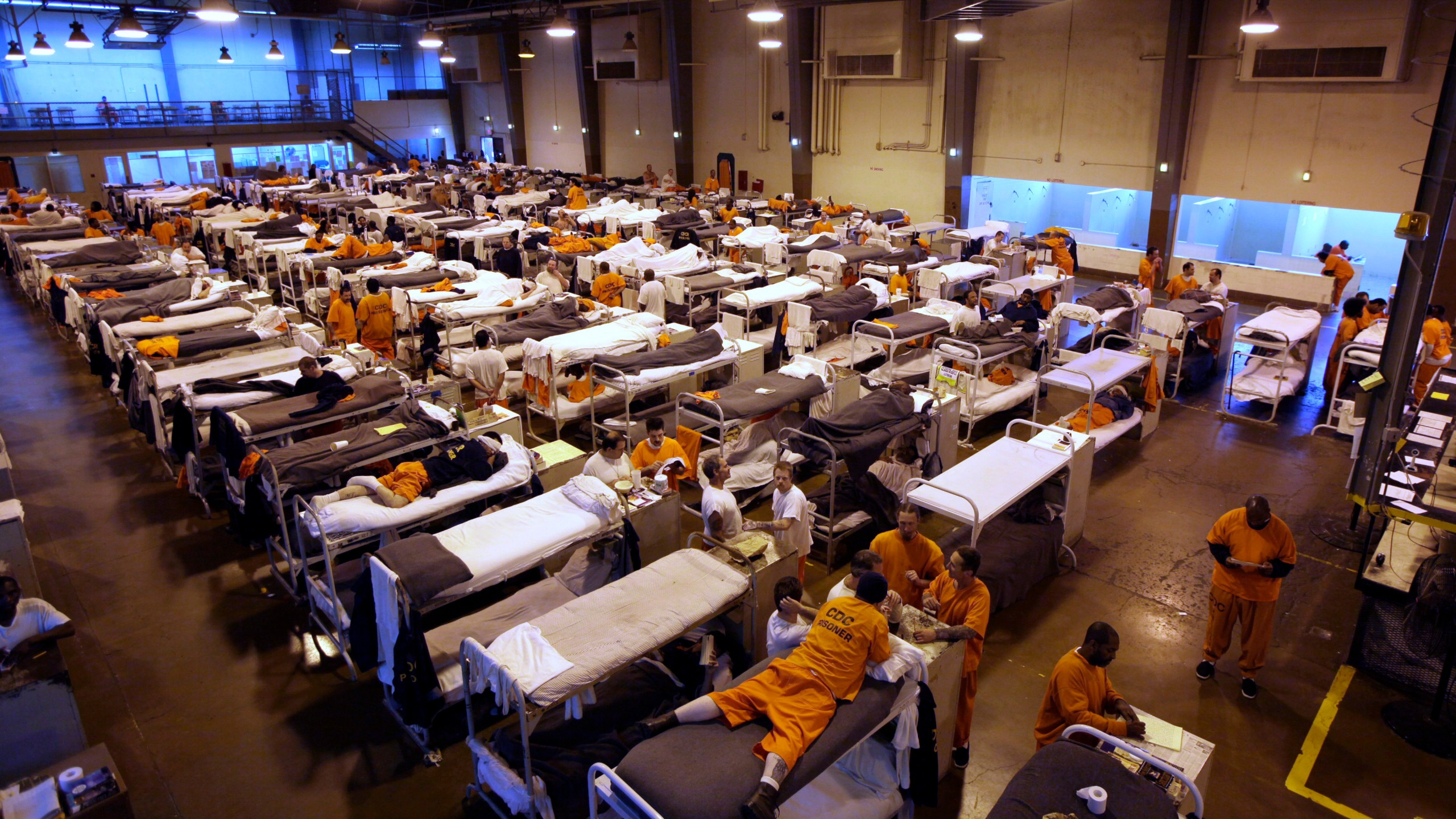 FILE - In this May 20, 2009 file photo, several hundred inmates crowd the gymnasium at San Quentin prison in San Quentin, California. A decade after prison crowding forced California to realign its criminal justice system, the population has shrunk to the point that officials on Tuesday, April 13, 2021, announced they will close one of the state's two inmate firefighter training centers along with portions of two other prisons, the second such announcement in months. (AP Photo/Eric Risberg, File)