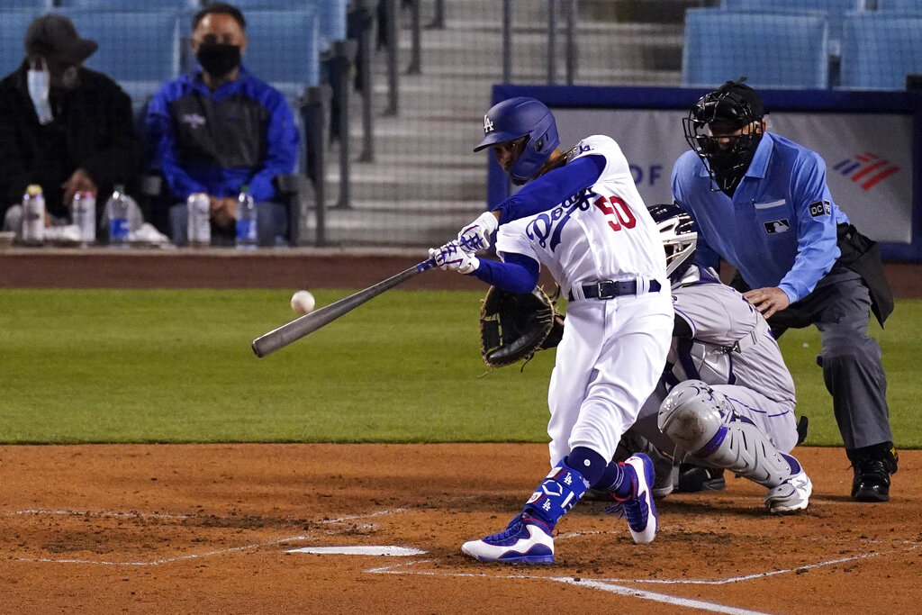 Los Angeles Dodgers' Mookie Betts, left, hits a solo home run as Colorado Rockies catcher Elias Diaz, center, watches along with home plate umpire Tom Hallion during the third inning of a baseball game Tuesday, April 13, 2021, in Los Angeles. (AP Photo/Mark J. Terrill)