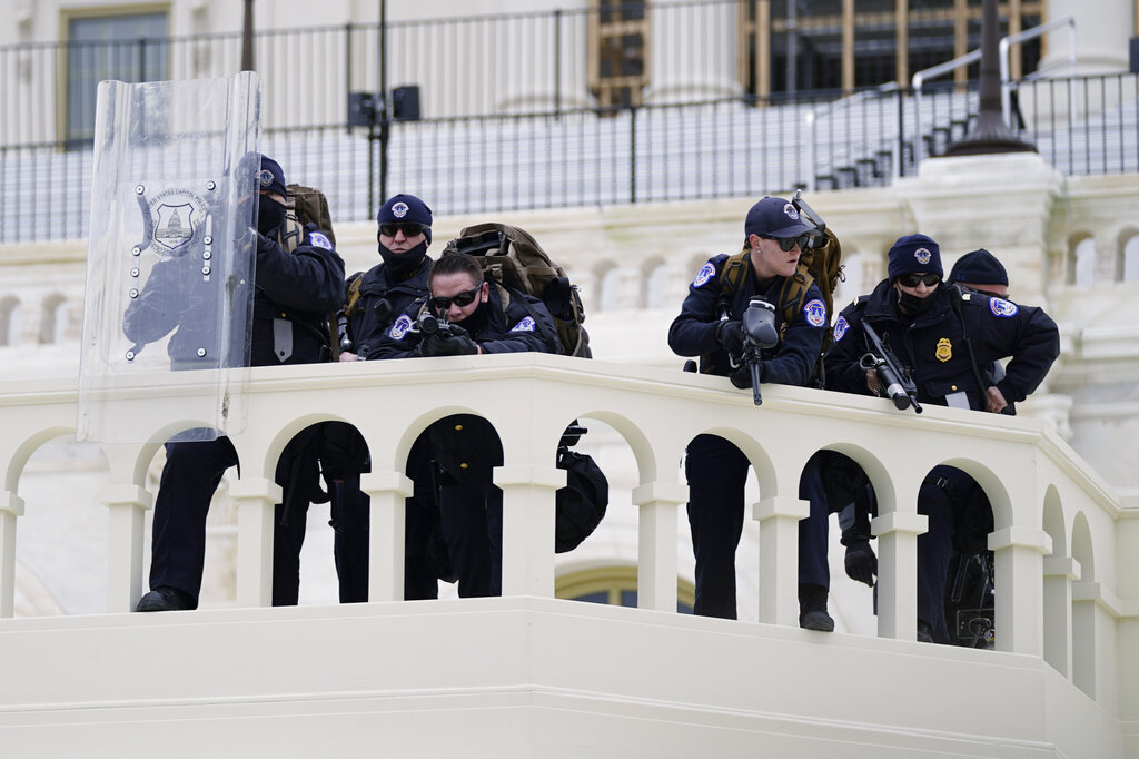 In this Jan. 6, 2021, file photo, police keep a watch on demonstrators who tried to break through a police barrier at the Capitol in Washington. (AP Photo/Julio Cortez, File)