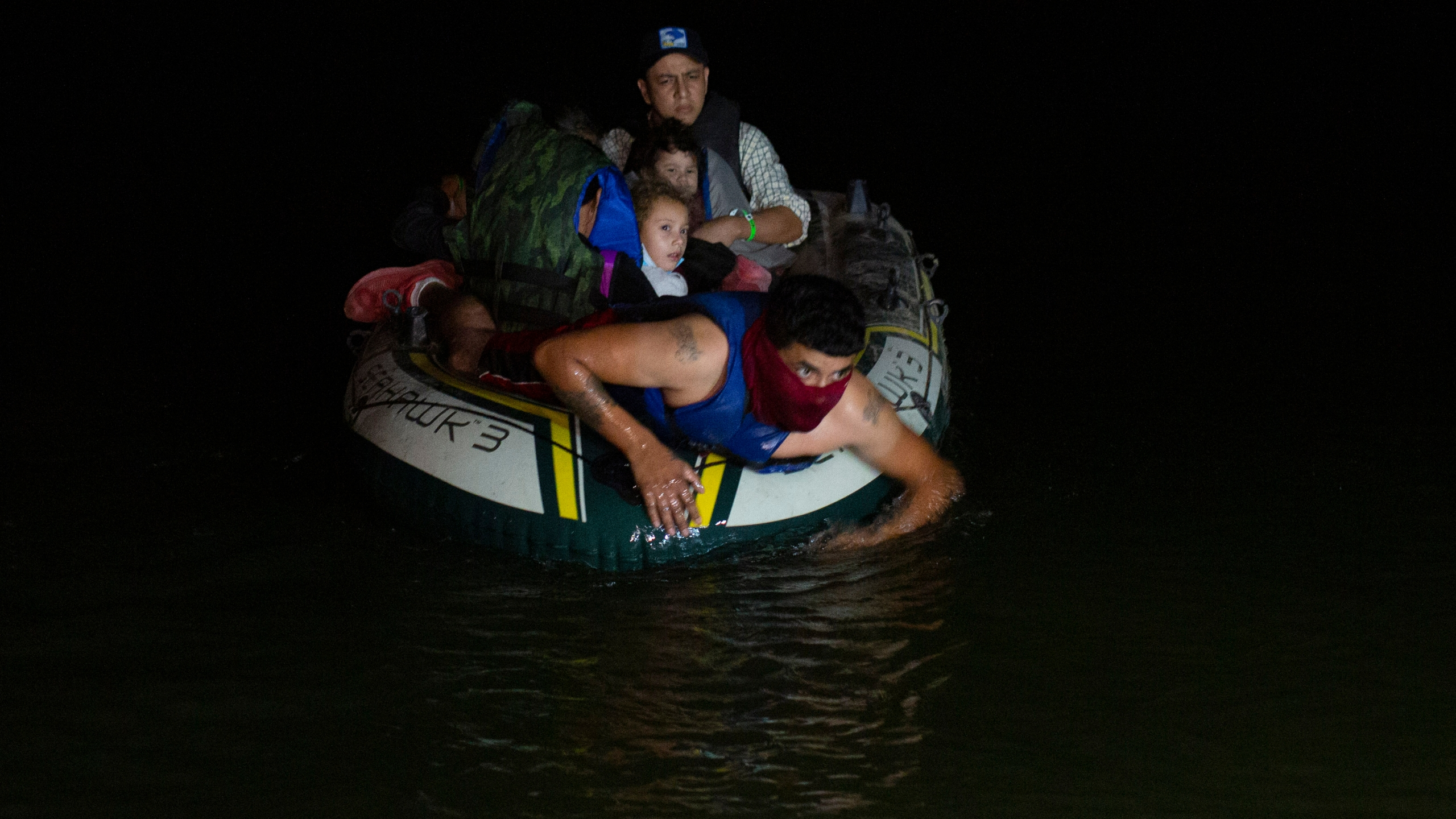 In this March 30, 2021 file photo, a smuggler takes migrants, mostly from Central American countries, on a small inflatable raft towards U.S. soil, in Roma, Texas. (Dario Lopez-Mills, Associated Press)