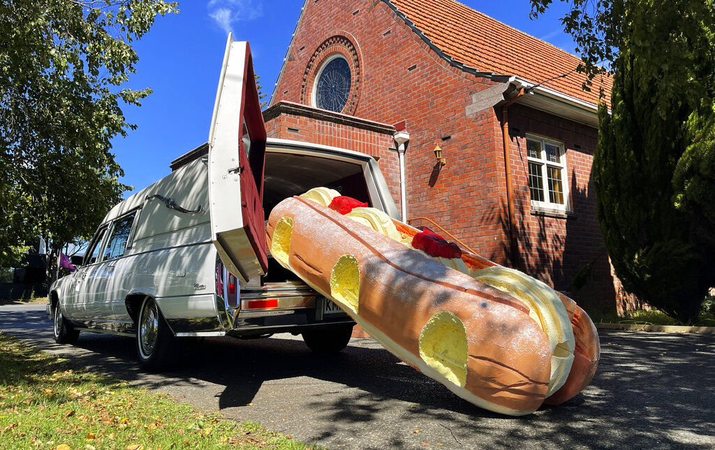 This photo provided by Ross Hall, shows a cream doughnut shaped coffin for the funeral of Phil McLean outside a church in Tauranga, New Zealand on Feb 17, 2021. (Ross Hall via AP)