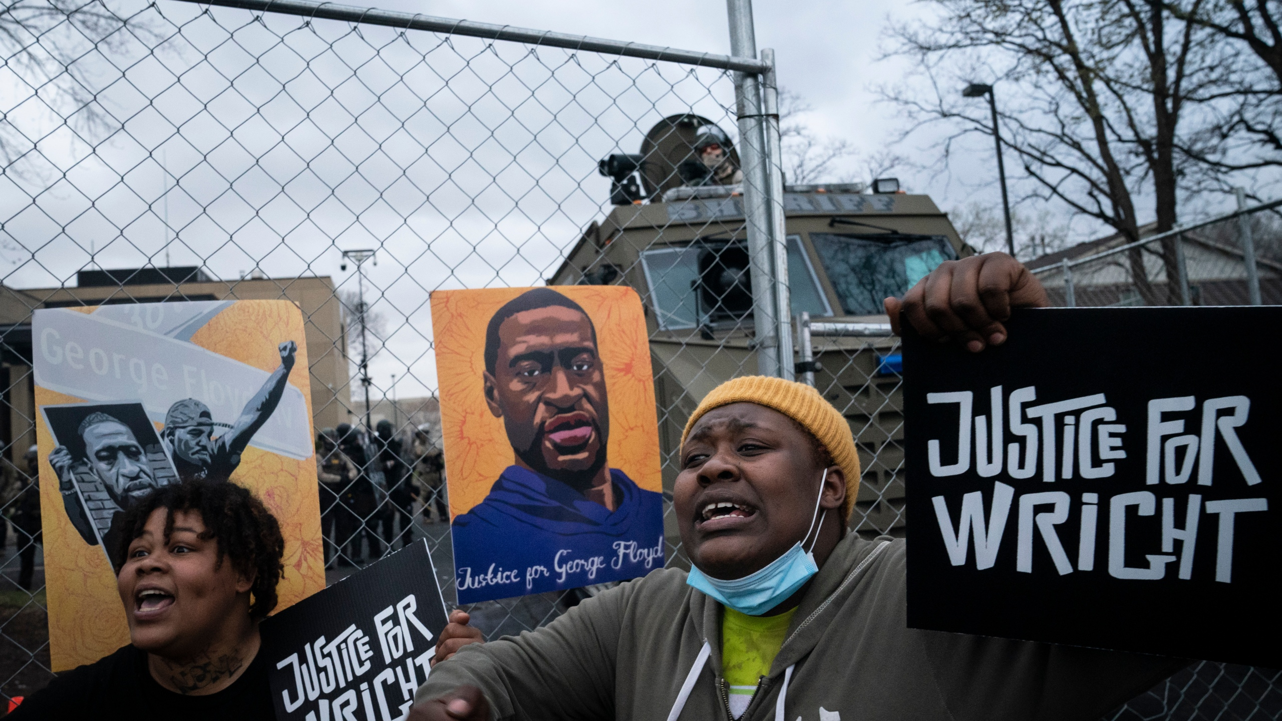 Demonstrators shout along a perimeter fence guarded by law enforcement officers during a protest over Sunday's fatal shooting of Daunte Wright during a traffic stop, outside the Brooklyn Center Police Department, Wednesday, April 14, 2021, in Brooklyn Center, Minn. (AP Photo/John Minchillo)