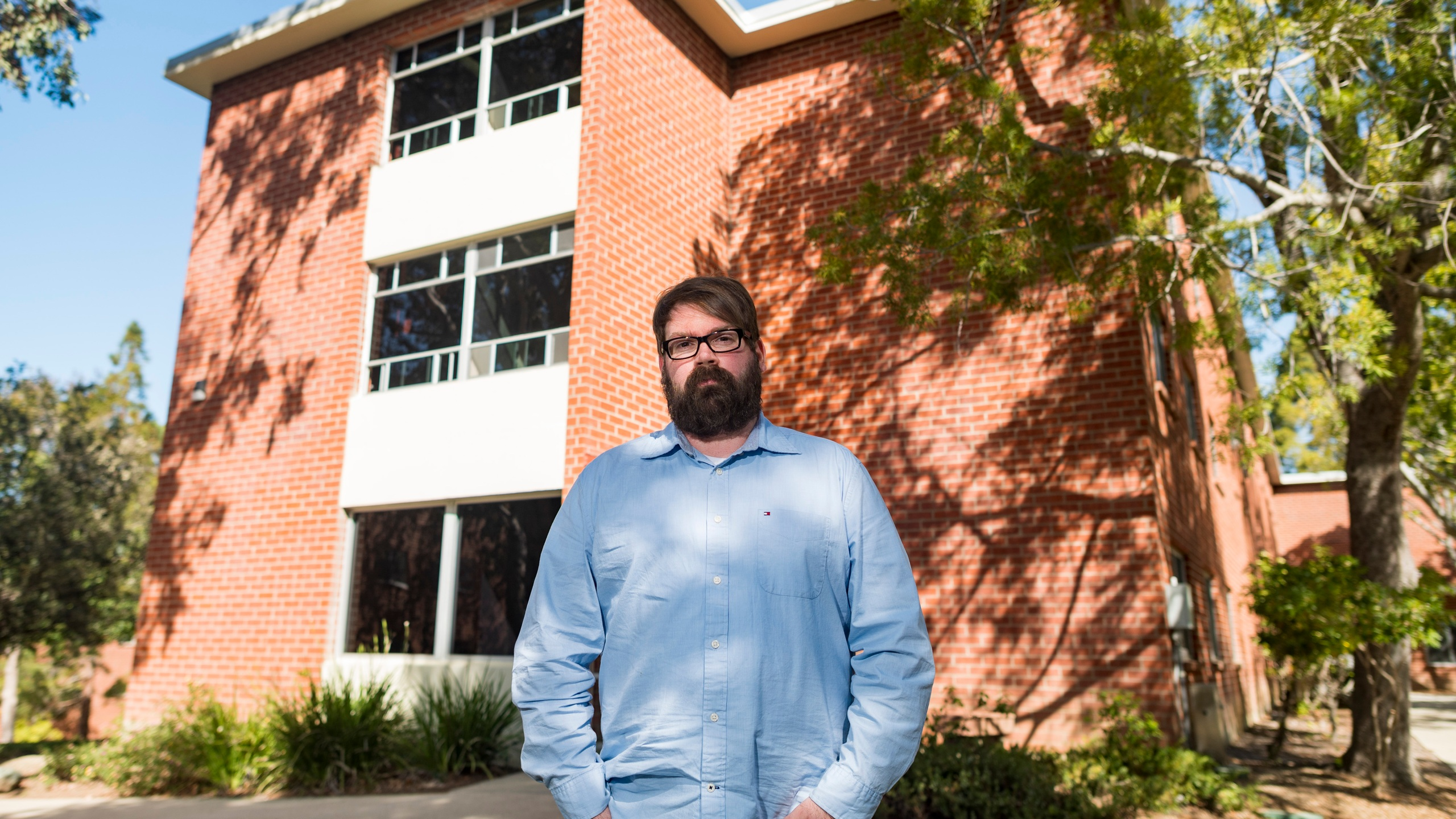 Chris Lambert, a musician and recording engineer, poses on April 15, 2021, in front of Muir Hall dormitory at California Polytechnic University in San Luis Obispo. (Nic Coury / Associated Press)