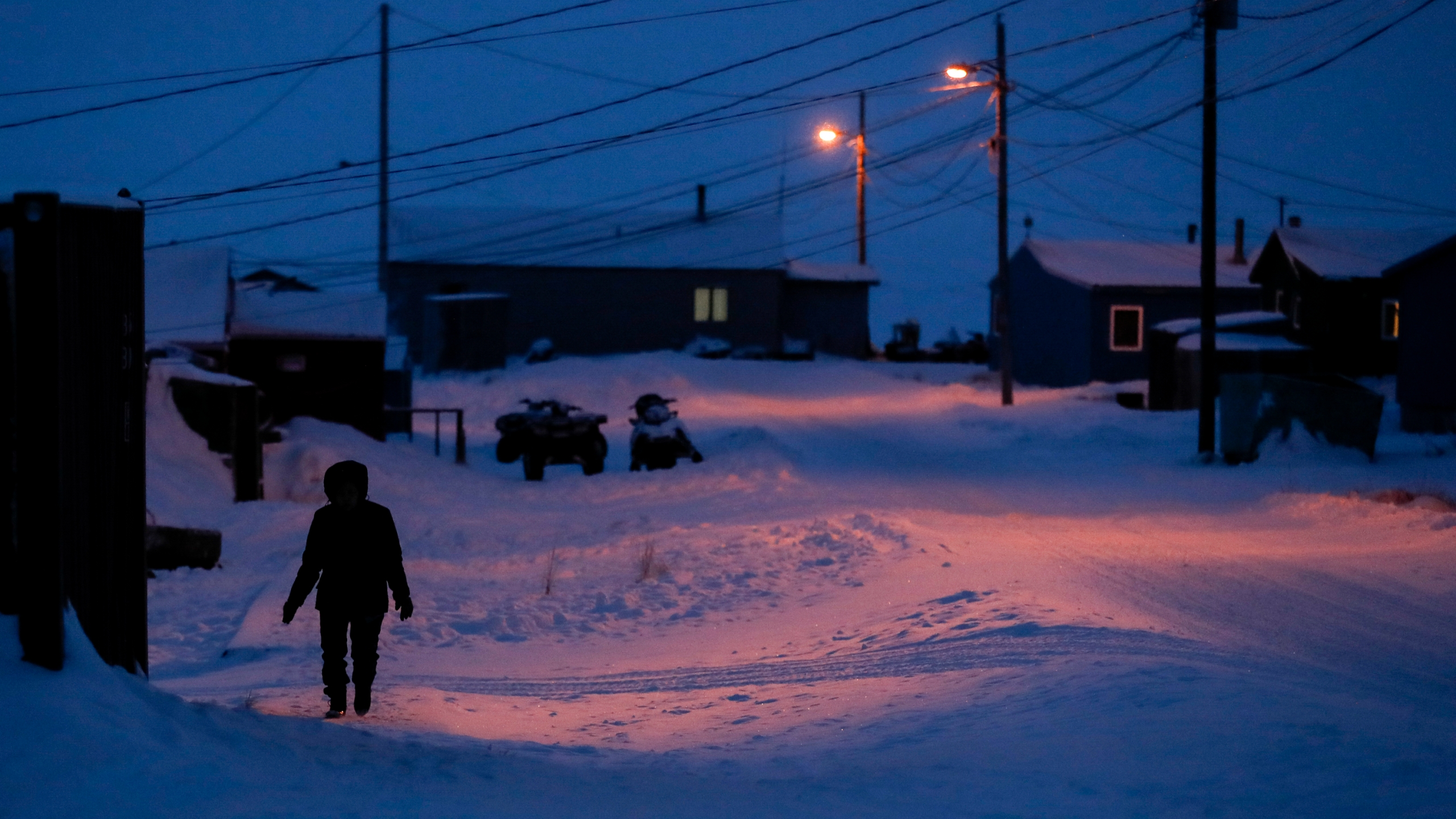 FILE - In this Jan. 20, 2020, file photo, a woman walks before dawn in Toksook Bay, Alaska, a mostly Yuip'ik village on the edge of the Bering Sea. The U.S. Supreme Court will hear oral arguments Monday, April 19, 2021, in a case that will determine who is eligible to receive more than $530 million in federal virus relief funding set aside for tribes more than a year ago. More than a dozen Native American tribes sued the U.S. Treasury Department to keep the money out of the hands of Alaska Native corporations, which provide services to Alaska Natives but do not have a government-to-government relationship with the United States. (AP Photo/Gregory Bull, File)
