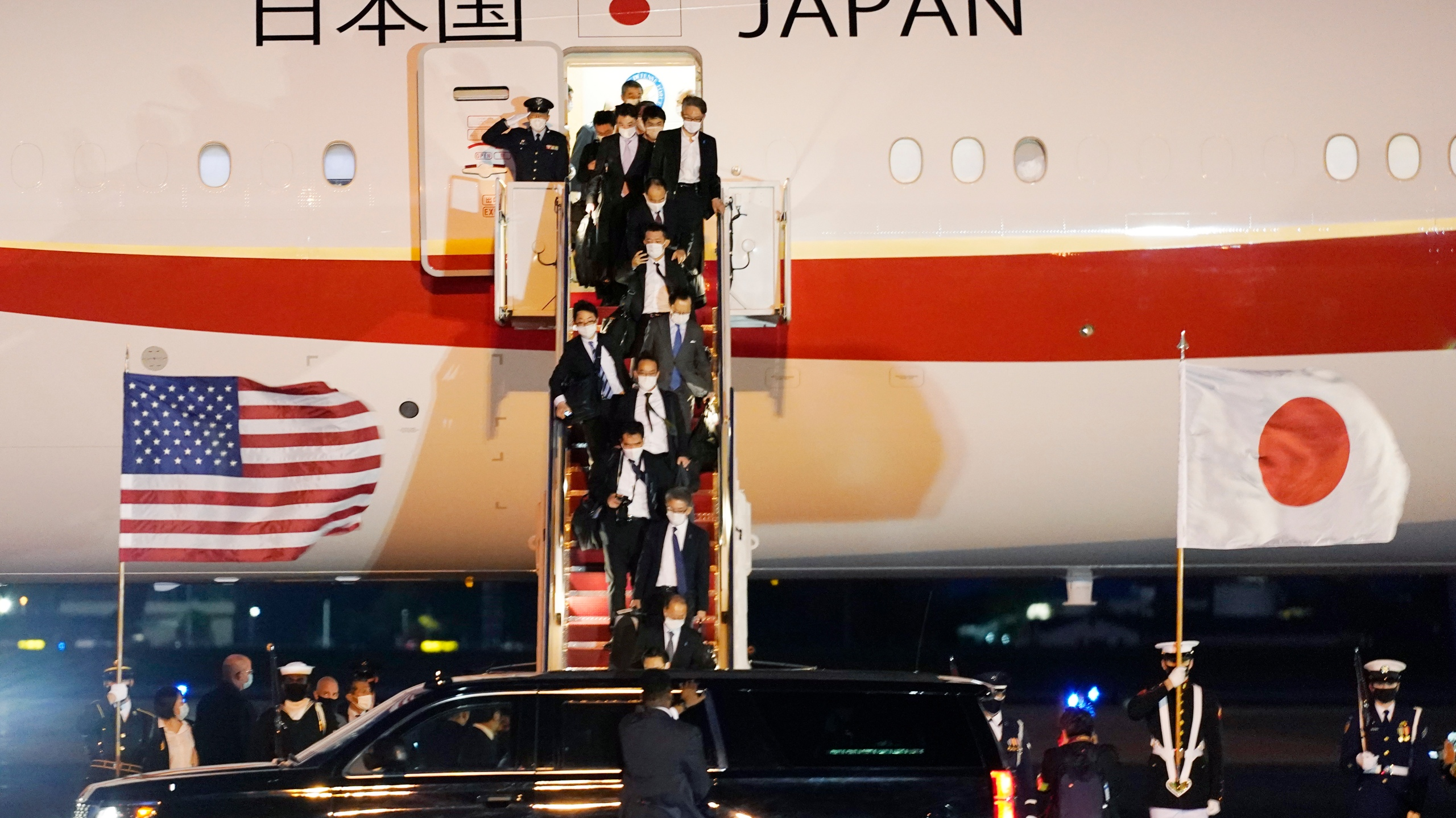 The Japanese delegation walks off the plane after Japanese Prime Minister Yoshihide Suga arrived at Andrews Air Force Base, Md., Thursday, April 15, 2021. Suga will be the first foreign leader to have a face-to-face meeting with President Joe Biden, when they meet at the White House on Friday. (AP Photo/Manuel Balce Ceneta)