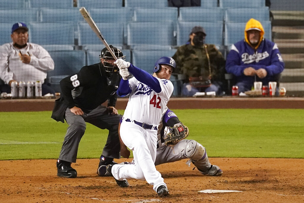 Los Angeles Dodgers' Max Muncy hits a home run during the seventh inning of a baseball game against the Colorado Rockies Thursday, April 15, 2021, in Los Angeles. Chris Taylor and Justin Turner also scored. (AP Photo/Ashley Landis)